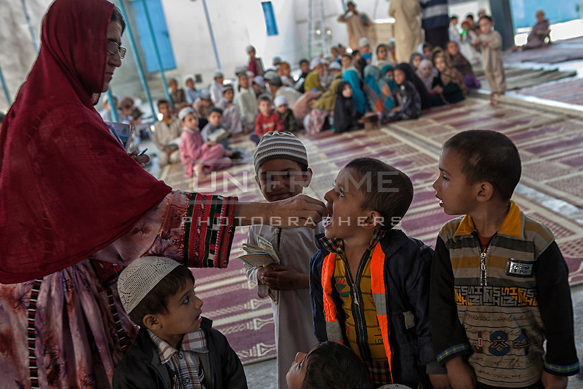 A Pakistani lady health worker administers polio drops to children, at the religious school, during 'Anti-polio campaign' in Karachi, Pakistan on Jan. 19, 2015