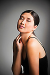Young Asian woman seated, gently touching her neck