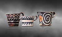 "Minoan Kamares ""eggshell"" ware cups with  with  polychrome decorations, from set found at Phaistos Palace 1800-1600 BC; Heraklion Archaeological  Museum, grey background.<br /> <br /> These cups found as parts of sets in Phaistos palace were names ""eggshell"" ware due to the very thin walls of the cups. This style of pottery is named afetr Kamares cave where this style of pottery was first found"
