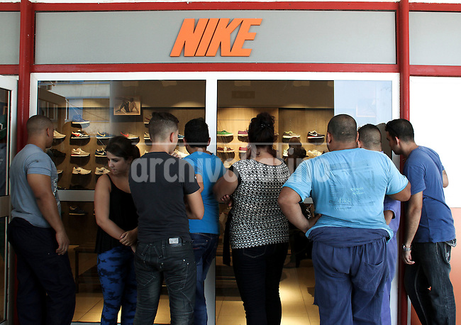 Cubans watch Nike sports shoes in a recently opened free store in Havana. This kind of store offers imported good freely