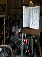 A clipboard with instructions hangs near machinery in the workshop of the Dale Guild Foundry.