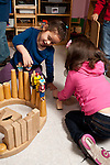 Education Preschool  4-5 year olds two girls playing together with human figures on top of blocks talking and interacting