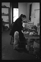 Lingtou Village, Kaihua County, Quzhou City, Zhejiang Province - A woman works at the kitchen accompanied by her pet dog, December 2020. Lingtou Village is located along the Qiantang River.