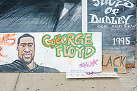 A painting of George Floyd, a Minneapolis man killed by police on May 25, 2020, is seen next to a mural in Nubian Square in Boston, Massachusetts, on Sun., June 7, 2020.