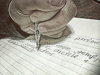 Left handed high school student writes chemistry class notes the night before a mid-term exam.