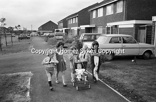 1970s children. A group of young kids walking to the shops and pushing baby sister in her pram. They are very smartly dressed living in a modern housing development 1977 Milton Keynes Buckinghamshire 1970s UK