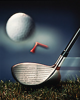 A golf ball in motion having been powerfully hit by a driver with a broken tee in action.