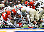 Notre Dame Fighting Irish running back Robert Hughes (33) gets tackled by Miami Hurricanes defensive lineman Micanor Regis (54) and Miami Hurricanes linebacker Sean Spence (31) during the 2010 Hyundai Sun Bowl football game between the Notre Dame Fighting Irish and the Miami Hurricanes at the Sun Bowl Stadium in El Paso, Tx. Notre Dame defeats Miami 33 to 17...