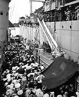 Vietnam refugees.  USS Montague lowers a ladder over the side to French LSM to take refugees aboard.  Haiphong, August 1954.  PH1 H.S. Hemphill.  (Navy)<br /> EXACT DATE SHOT UNKNOWN<br /> NARA FILE #:  080-G-644449<br /> WAR & CONFLICT BOOK #:  386
