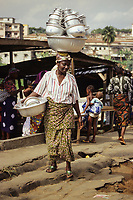 Cote d'Ivoire, Ivory Coast, Abidjan.  Woman Carrying an Assortment of Pots and Cooking Utensils on her Head Navigates Ruts in the Walkway.
