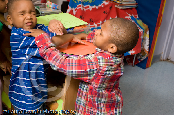 Preschool ages 3-5 two boys physically fighting conflict argument horizontal