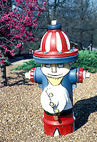 Fire Hydrant painted as minature Uncle Sam-- US Government character-- adorns public park in spring