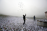 """A Tibetan man throws small pieces of paper, called """"wind horses,"""" into the air, next to a stupa on top of a mountain on the Tibetan Plateau. This practice is is said to bring good luck and a safe journey."""