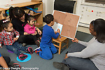 Education Preschool 2-3 year olds in all-day program circle time boy paticipating in discussion of schedule