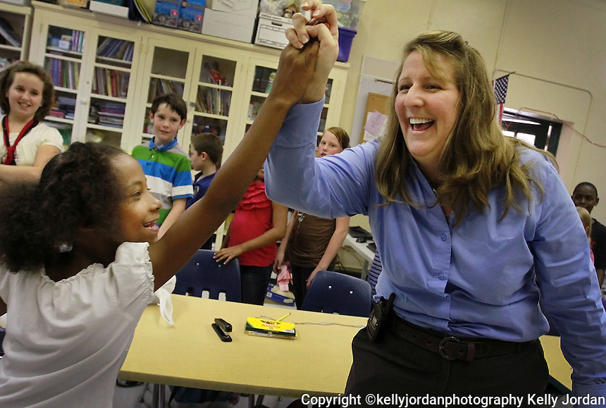 Kelly.Jordan@jacksonville.com--052611--Ortega Museum Magnet Elementary School principal Stephanie Shepard gives a high five to Smajah Locklear as she visits a classroom of third grade students after they found out their reading FCAT scores went up 33 points Thursday May 26, 2011. The entire class lined up to get high fives from their principal along with their language arts teachers Sharon Caruso and Christopher Watson as the news of their scores came in.(The Florida Times-Union, Kelly Jordan)