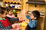 Preschool 3 year olds game of store in family area two girls and a boy playing together