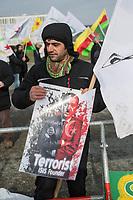 """Kurden-Protest vor dem Kanzleramt anlaesslich des Besuch des tuerkischen Ministerpraesidenten Binali Yildirim bei Bundeskanzlerin Angela Merkel.<br /> Die Demonstranten forderten den Abzug tuerkischer Truppen aus dem Norden von Syrien, wo die Tuerkei die Stadt Afrin angreift um die dort lebenden Kurden zu vertreiben. Zudem forderten die Demonstranten, dass die Bundesregierung die Unterstuetzung der Tuerkei mit Waffen und Panzern beenden soll.<br /> Im Bild: Ein Demonstrant haelt ein Plakat auf dem der Tuerkische Praesident als Terrorist und Gruender der islamistischen Terrororganisation """"Islamischer Staat"""" bezeichnet wird.<br /> 15.2.2018, Berlin<br /> Copyright: Christian-Ditsch.de<br /> [Inhaltsveraendernde Manipulation des Fotos nur nach ausdruecklicher Genehmigung des Fotografen. Vereinbarungen ueber Abtretung von Persoenlichkeitsrechten/Model Release der abgebildeten Person/Personen liegen nicht vor. NO MODEL RELEASE! Nur fuer Redaktionelle Zwecke. Don't publish without copyright Christian-Ditsch.de, Veroeffentlichung nur mit Fotografennennung, sowie gegen Honorar, MwSt. und Beleg. Konto: I N G - D i B a, IBAN DE58500105175400192269, BIC INGDDEFFXXX, Kontakt: post@christian-ditsch.de<br /> Bei der Bearbeitung der Dateiinformationen darf die Urheberkennzeichnung in den EXIF- und  IPTC-Daten nicht entfernt werden, diese sind in digitalen Medien nach §95c UrhG rechtlich geschuetzt. Der Urhebervermerk wird gemaess §13 UrhG verlangt.]"""