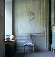 A chair in front of a wall lined with hand-painted linen canvas panels and Gustavian motifs that have faded over the passage of time
