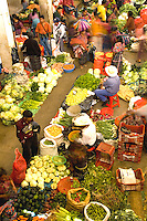 Local vendors in unusual birdseye angle from abovewith blurred movement in colorful printed clothes in fruit shopping center on market day in village of Chichicastenango Guatemal