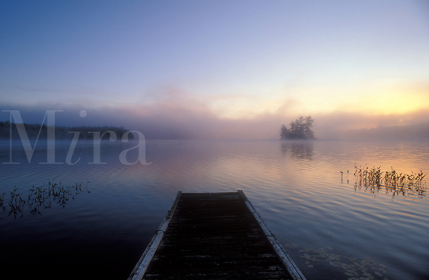 Canada, Ontario, Mackay Lake, sunrise on lake with  wooden pier and island in distance