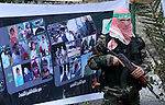 A Palestinian Hamas militant stands in front of a poster to Palestinian martyrs during a rally marking the 2nd anniversary of Israeli war on Gaza Strip, in Gaza City on January 1, 2011. Photo by Mohammed Asad