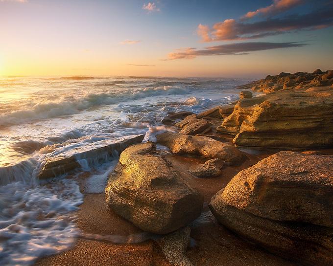 The surf crashing along the Atlantic shoreline, backlit by the rising sun.