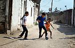 Three Roma children play football (soccer) in Suto Orizari, the Macedonian municipality that is Europe's largest Roma settlement.