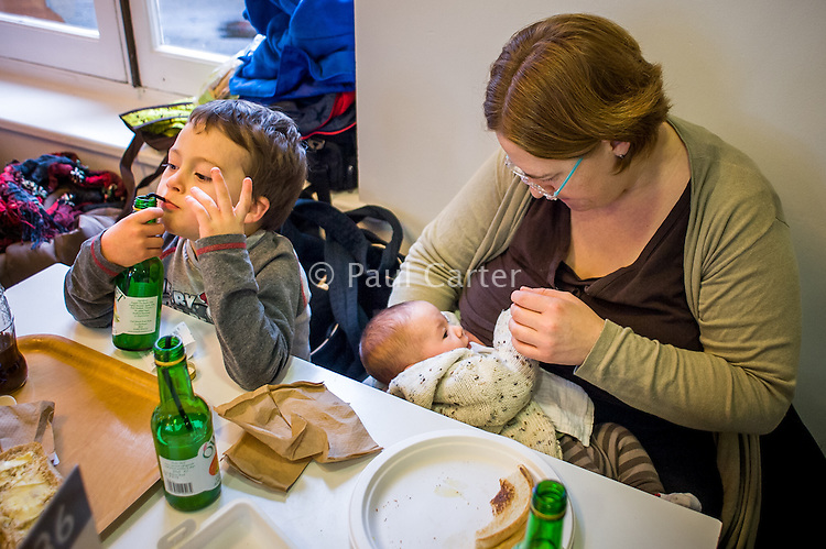 A mother breastfeeding her baby in a museum cafe while her older son drinks juice from a bottle with a straw.<br /> <br /> London, England, UK<br /> 08/03/2015<br /> <br /> © Paul Carter / wdiip.co.uk