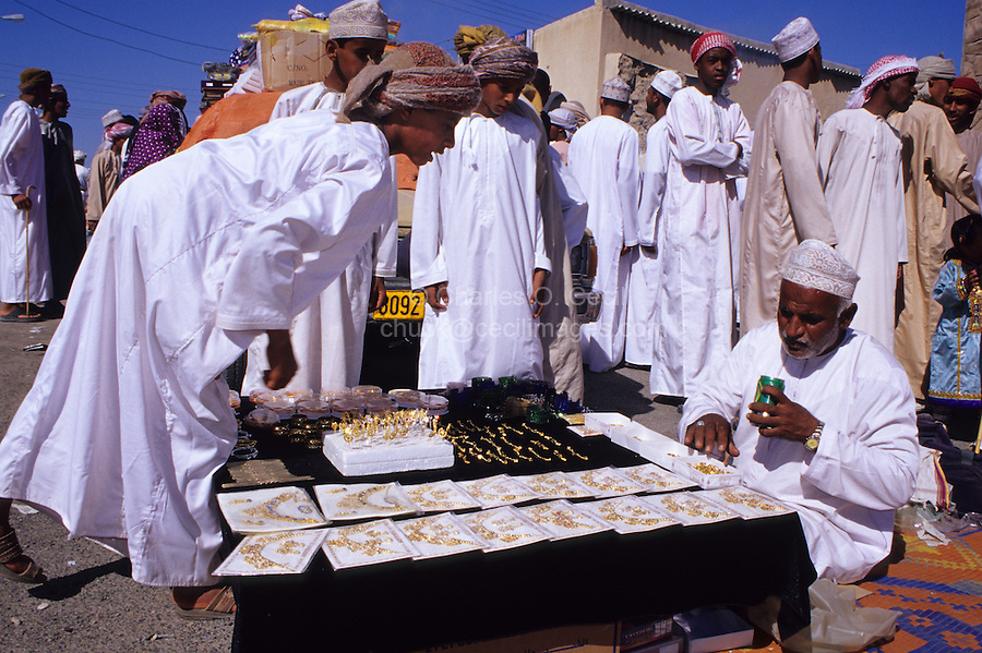 Mudayrib, Oman, Middle East - Omani boy shopping for a golden trinket for his sister as a gift for Eid al-Adha, the annual feast through which Muslims commemorate God's mercy in allowing Abraham to sacrifice a goat instead of his son, to prove his faith.
