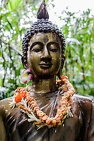 Close-up of a Buddha statue with lei at the Harold L. Lyon Arboretum and Botanical Garden, Honolulu, O'ahu.