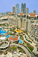 Al Murooj Rotana Hotel and apartments, pool and recreation area, tall buildings on Sheikh Zayed Road in the background.  Dubai. United Arab Emirates.