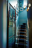 A view past on open glass door towards a staircase into a hallway with blue painted tongue and grove panelling.