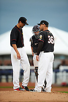 Quad Cities River Bandits pitching coach Dave Borkowski (36) talks with pitcher Justin Ferrell (45) and catcher Garrett Stubbs (17) during the first game of a doubleheader against the Wisconsin Timber Rattlers on August 19, 2015 at Modern Woodmen Park in Davenport, Iowa.  Quad Cities defeated Wisconsin 3-2.  (Mike Janes/Four Seam Images)
