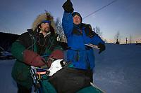 H.Neff arrives @ Ruby w/dog *Dozer* in basket gets directions from checker 2006 Iditarod AK Winter