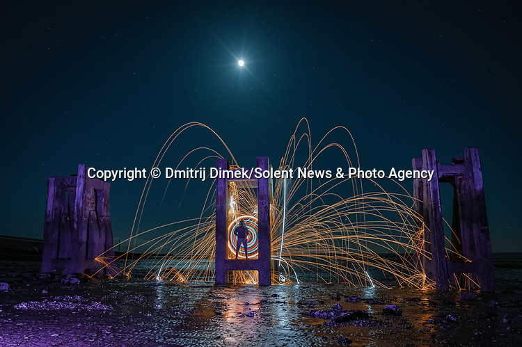 "Pictured:  Gunners Park in Shoeburyness, Essex.<br /> <br /> Amazing photos show sparks illuminating British landmarks as they fly from what appears to be a disc of colourful light.  This unique effect is the result of long-exposure night-time shots of a whisk stuffed with steel wool, which is set alight and spun at the end of a metal chain.<br /> <br /> Amateur photographer Dmitrij Dimek is passionate about what he calls 'light paintings', and took these photos at castles, beaches and other settings around Essex and London.  The 38 year old, who grew up in Poland but now lives in Southend-on-Sea, Essex, said: ""When I first found out about light painting with steel wool, I thought it was an outstanding way to connect with photography.  SEE OUR COPY FOR DETAILS.<br /> <br /> Please byline: Dmitrij Dimek/Solent News<br /> <br /> © Dmitrij Dimek/Solent News & Photo Agency<br /> UK +44 (0) 2380 458800"