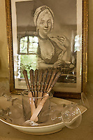 A glass filled with antique knives and a collection of wine glasses in a bowl are displayed on the mantelpiece in the dining room