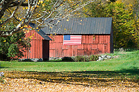 An old red barn with an American flag hanging on the side and autumn foliage on the hill behind, Vermont, New England, United States of America, North America