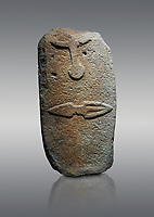 Late European Neolithic prehistoric Menhir standing stone with carvings on its face side. The representation of a stylalised male figure starts at the top with the bottom of a carving of a falling figure with head at the bottom and 2 curved arms encircling a body above. at the bottom is a carving of a dagger running horizontally across the menhir. Excavated from Piscina 'E Sali V site,  Laconi. Menhir Museum, Museo della Statuaria Prehistorica in Sardegna, Museum of Prehoistoric Sardinian Statues, Palazzo Aymerich, Laconi, Sardinia, Italy. Grey background.