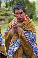 Peru, Urubamba Valley, Quechua Village of Misminay.  Village Man Performing a Welcoming Ceremony for Guests, with Coca leaves.