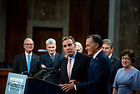 United States Senator Mark Warner (Democrat of Virginia), left, is embraced by United States Senator Mitt Romney (Republican of Utah) as he makes remarks after the vote on the motion to invoke cloture to proceed to the consideration of H.R. 3684, the INVEST in America Act on Capitol Hill in Washington, DC on Wednesday, July 28, 2021. The vote to begin discussion of the bipartisan infrastructure bill agreed to by the White House, was 67 to 32. If passed, the bill would invest close to $1 trillion in roads, bridges, ports and other infrastructure without a major tax increase.<br /> Credit: Rod Lamkey / CNP / MediaPunch