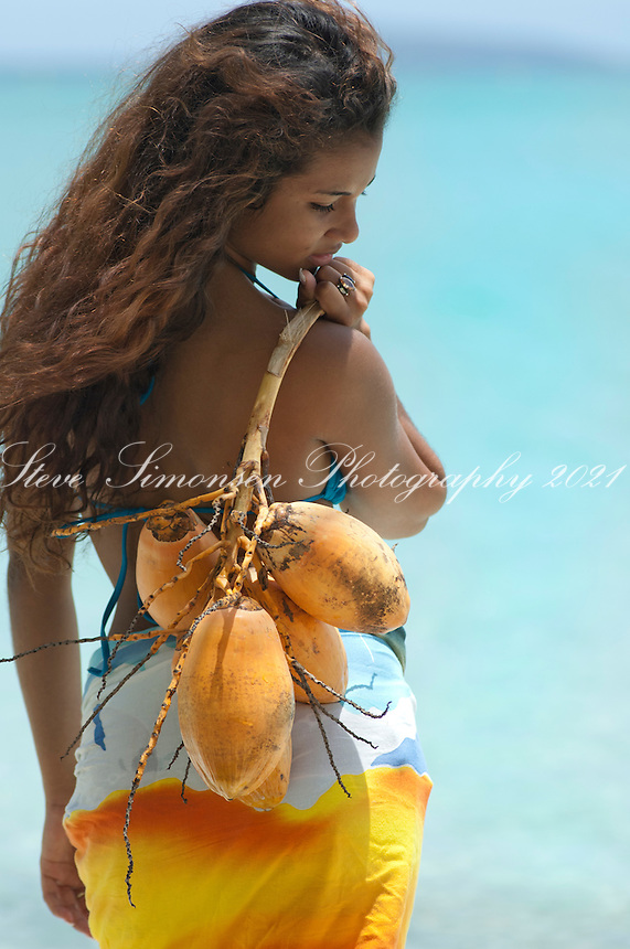 Aldris Santana holding a string of coconuts at Maho Bay.Virgin Islands National Park.St. John, U.S. Virgin Islands