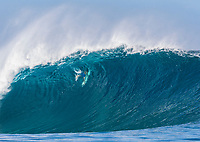 A surfer duck dives a large wave on the North Shore of O'ahu.