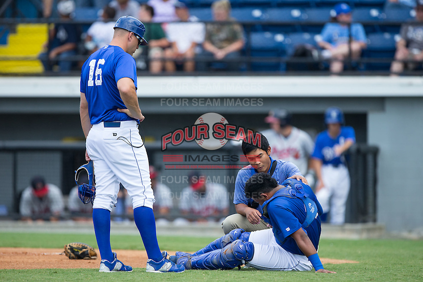 Burlington Royals trainer Saburo Hagihara and manager Scott Thorman (16) check on catcher Meibrys Viloria (4) after he was hit in the right shoulder with a foul ball during the game against the Danville Braves at Burlington Athletic Park on July 12, 2015 in Burlington, North Carolina.  The Royals defeated the Braves 9-3. (Brian Westerholt/Four Seam Images)