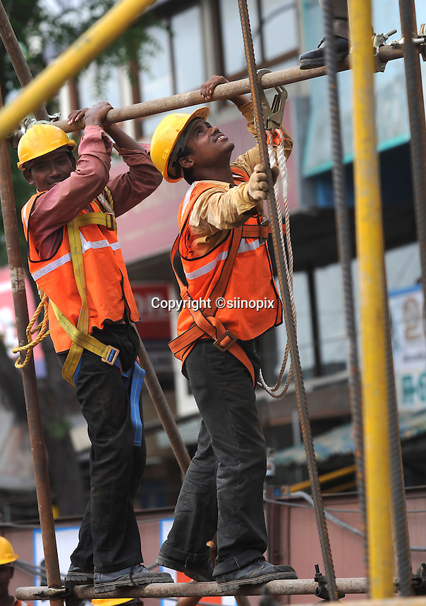 Workers with safety rope attached works on the scaffolding at the constructino site in Madras, India