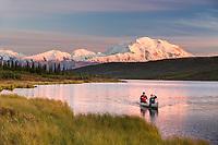 Man and women in a canoe in Wonder Lake as alpenglow light falls on Mt. Denali, Denali National Park, Interior, Alaska