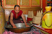 Buddhist Gelugpa monk makes tsampa, with roasted barley flour, water and yak butter at Sera monastery, Lhasa, Tibet, China.