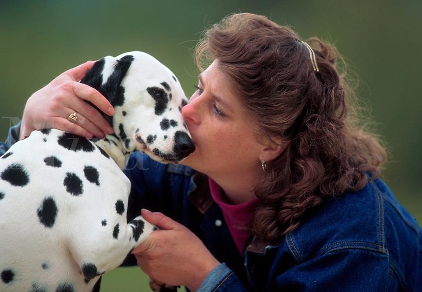 Woman kisses her dalmatian.