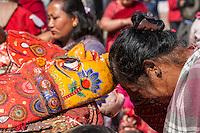 Bhaktapur, Nepal.  Woman Venerating Mask Representing Hindu Deity.