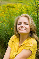 Blonde woman wearing yellow dress posing in front of goldenrod