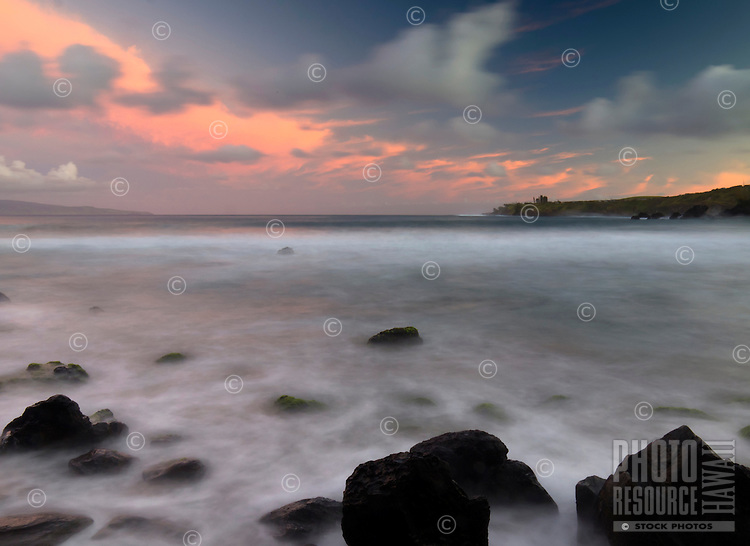 The slow shutter speed of a camera softens the rough water around the shoreline stones of Makule'ia Bay, Maui.